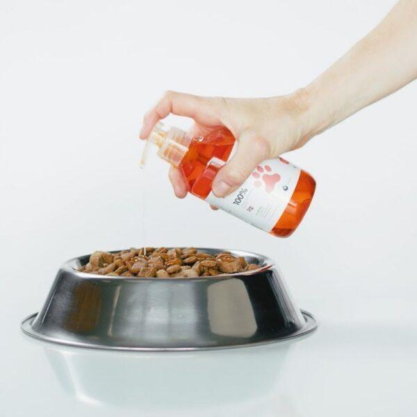 בן אדם מפזר שמן סלמון על מזון לכלבים